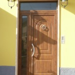 Porta di ingresso chiusa con pannello in alluminio finto legno, accessori inox