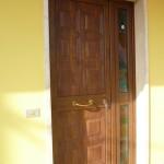 Porta di ingresso chiusa con pannello in alluminio finto legno, accessori ottone